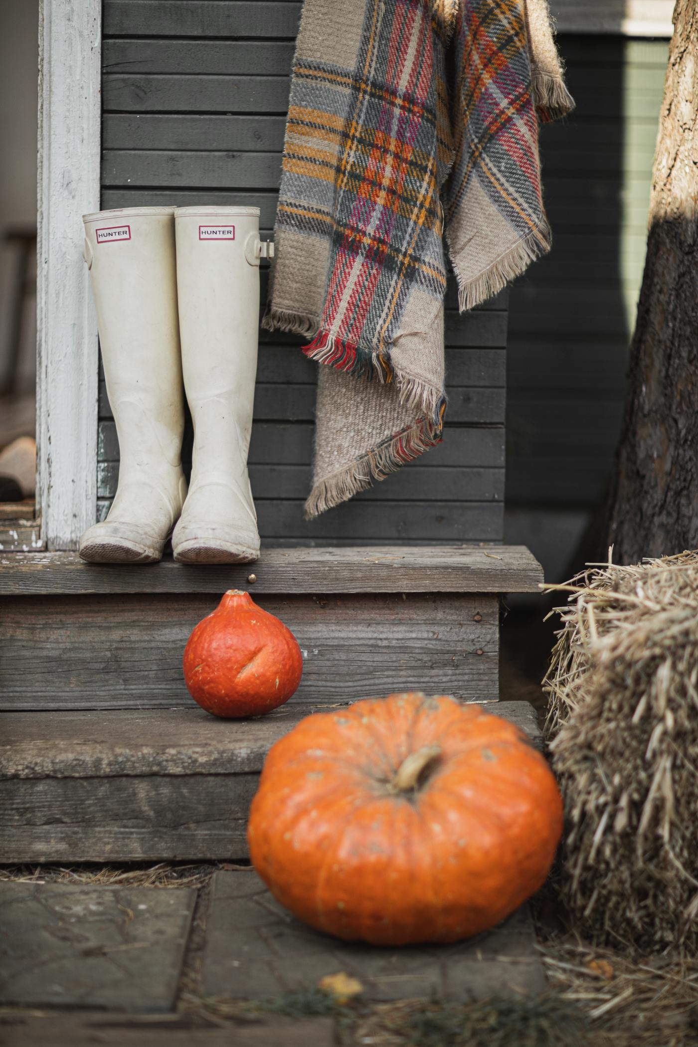 rustic front porch with two pumpkins, a haystack, white rubber boots, and a wool blanket