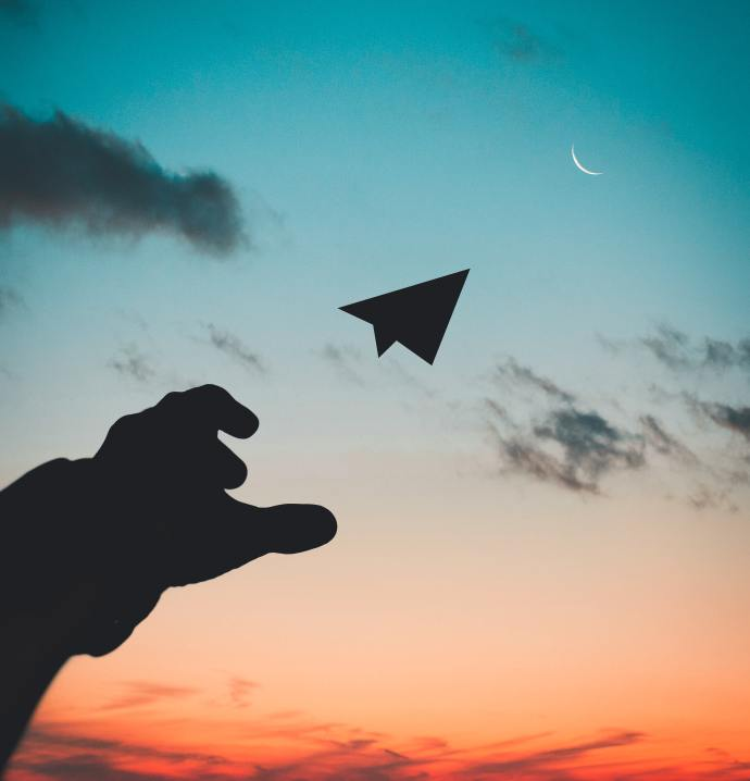 hand throwing a paper airplane into the sky with a sunset background