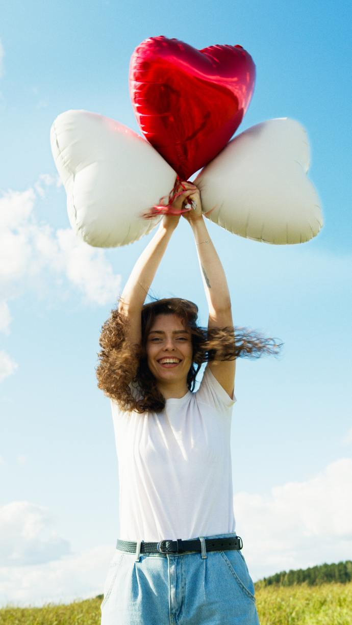 girl holding up heart balloons into the air and smiling
