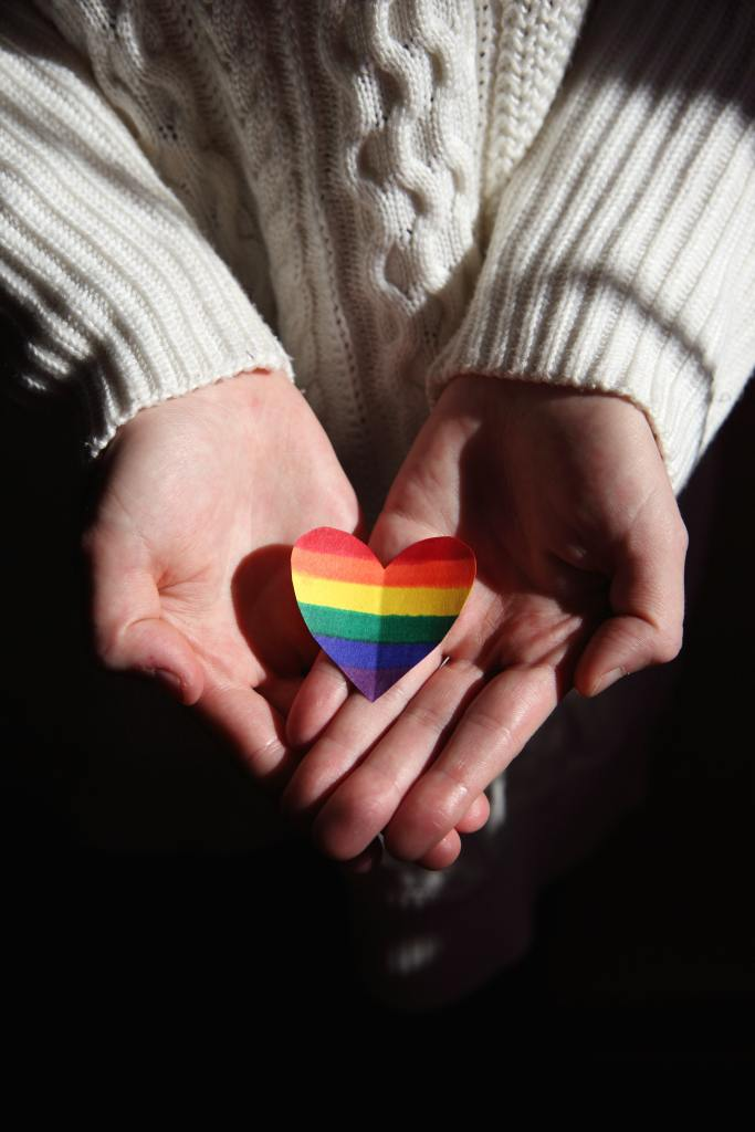 rich rainbow-colored small, paper heart in the hands of a female wearing white sweater