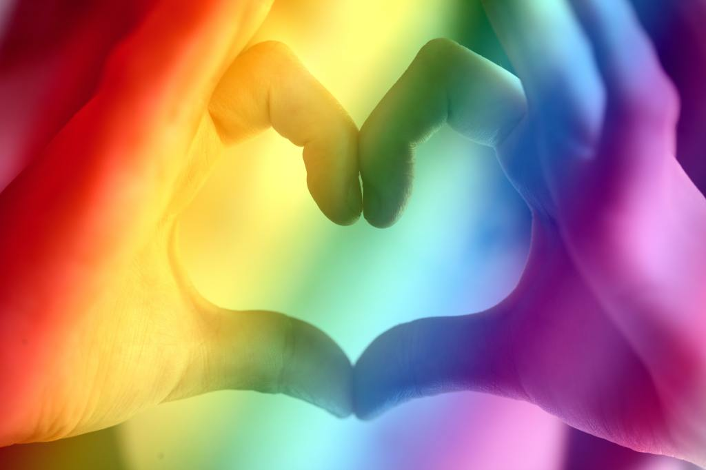 rich rainbow-colored background with hands creating a heart