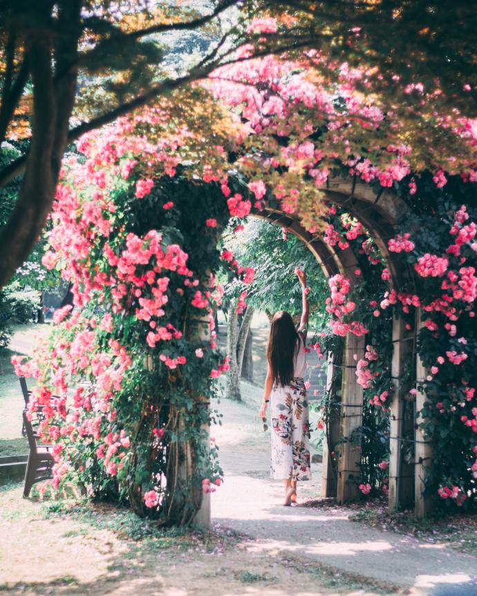 spring flowers on a trellis with a girl walking underneath wearing a white flowered skirt