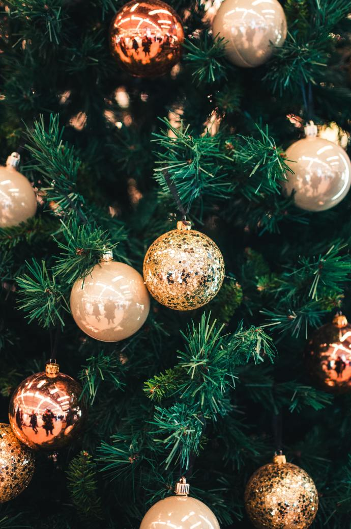 part of a Christmas tree with gold ball ornaments