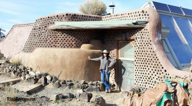 Vilma Reynoso standing in front of an earthship in New Mexico