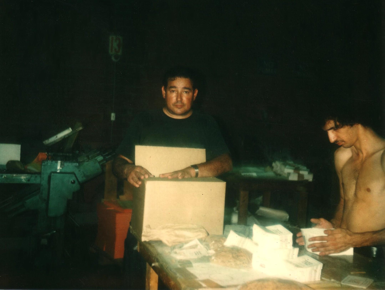 Hispanic man working at a bookbinding company assembling boxes