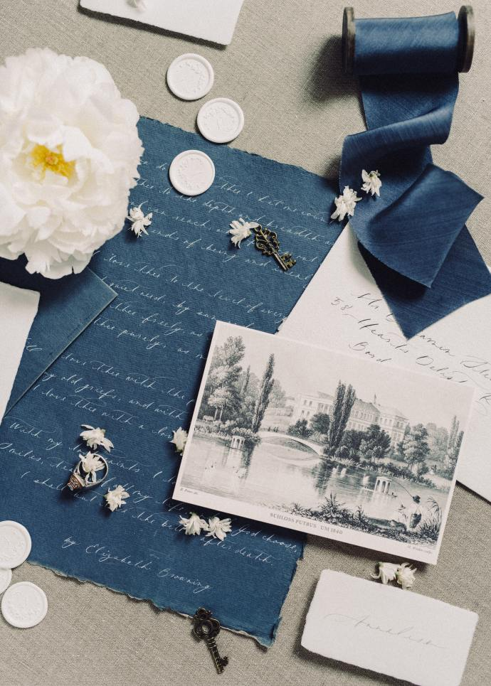 Scrapbooking items. White buttons, blue paper with a handwritten letter, black and white photograph, a spool of blue ribbon and a white carnation
