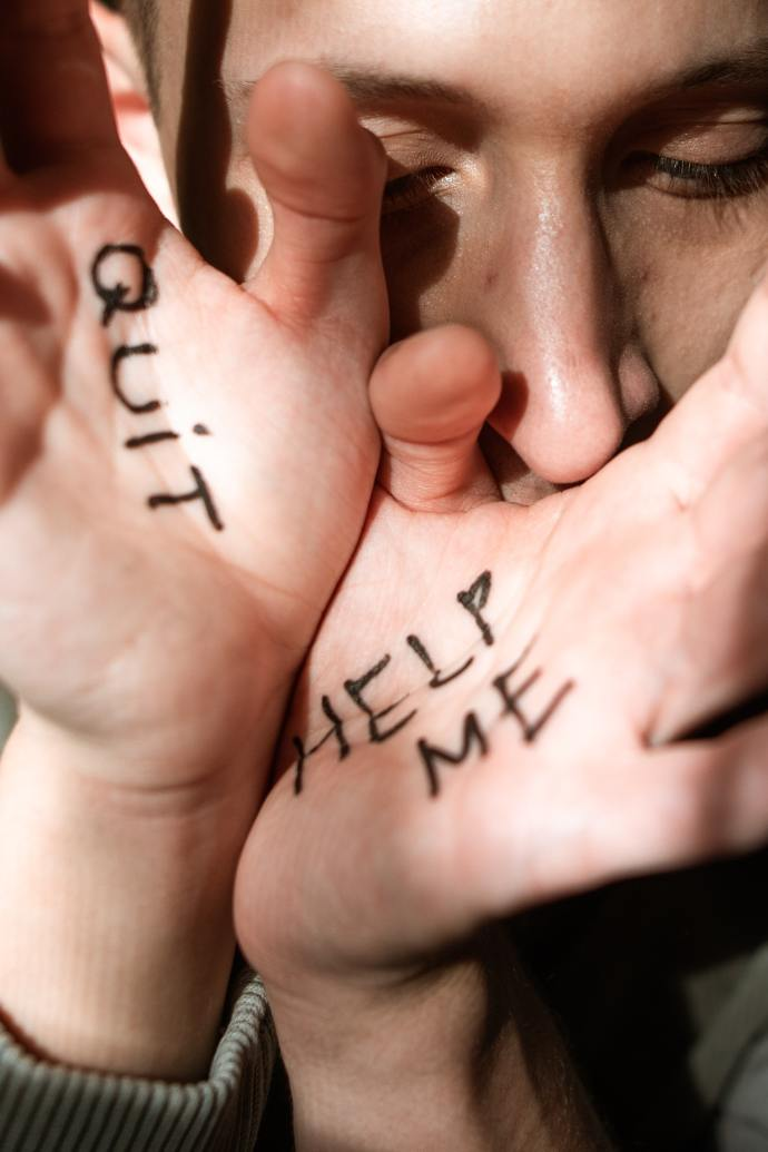 woman's hands in front of her face. On one hand is written Quit and on the other is written Help Me. Me too.