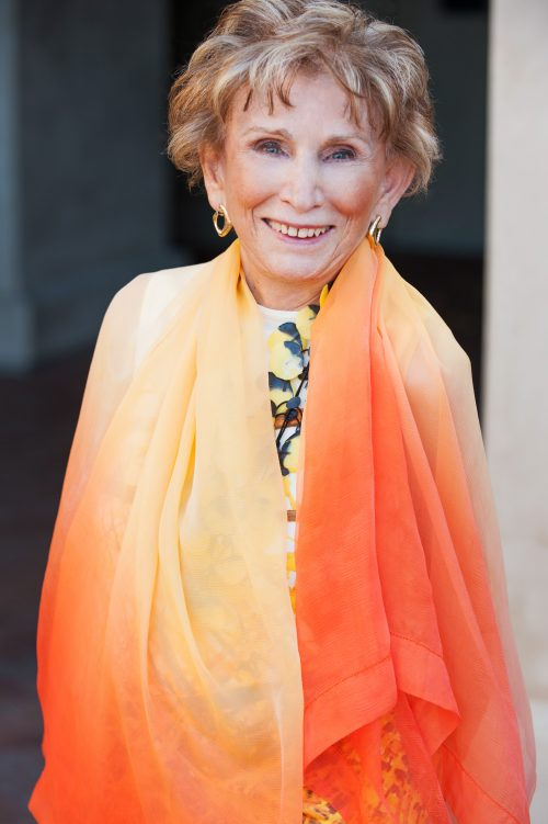 Eva Eger in orange dress, author of The Choice: Embrace the Possible, Book Review