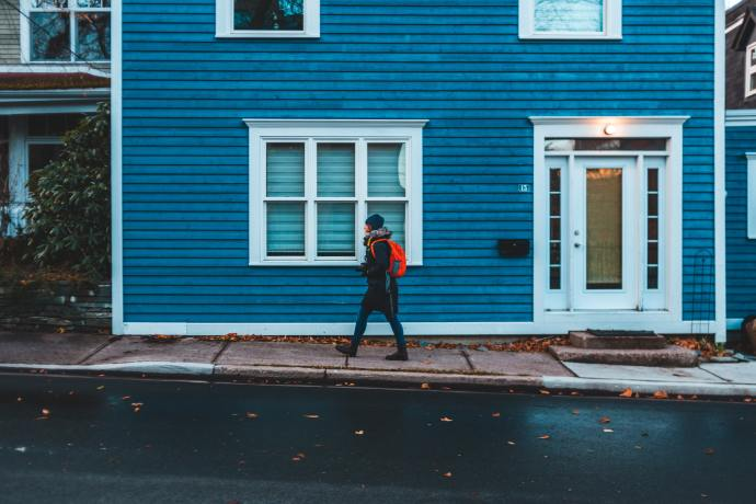 person walking in front of a big, blue house