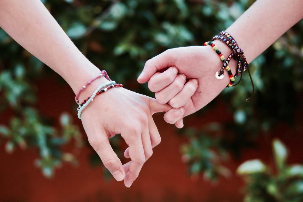 two female hands locking pinky fingers and wearing bead bracelets with a green tree background