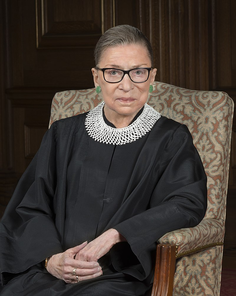 Ruth Bader Ginsburg on a chair with her judicial outfit