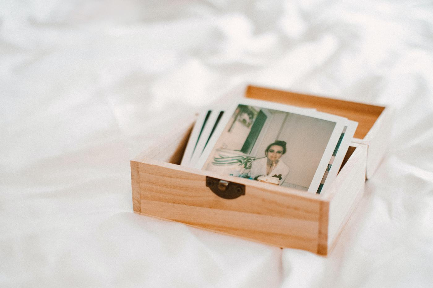 small wooden box with photographs over a white sheet
