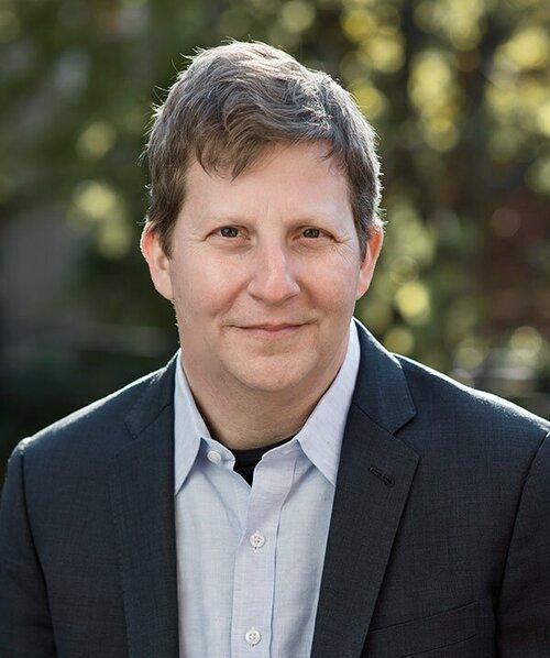 Headshot of Robert Kolker in a light blue shirt with a dark blue jacket