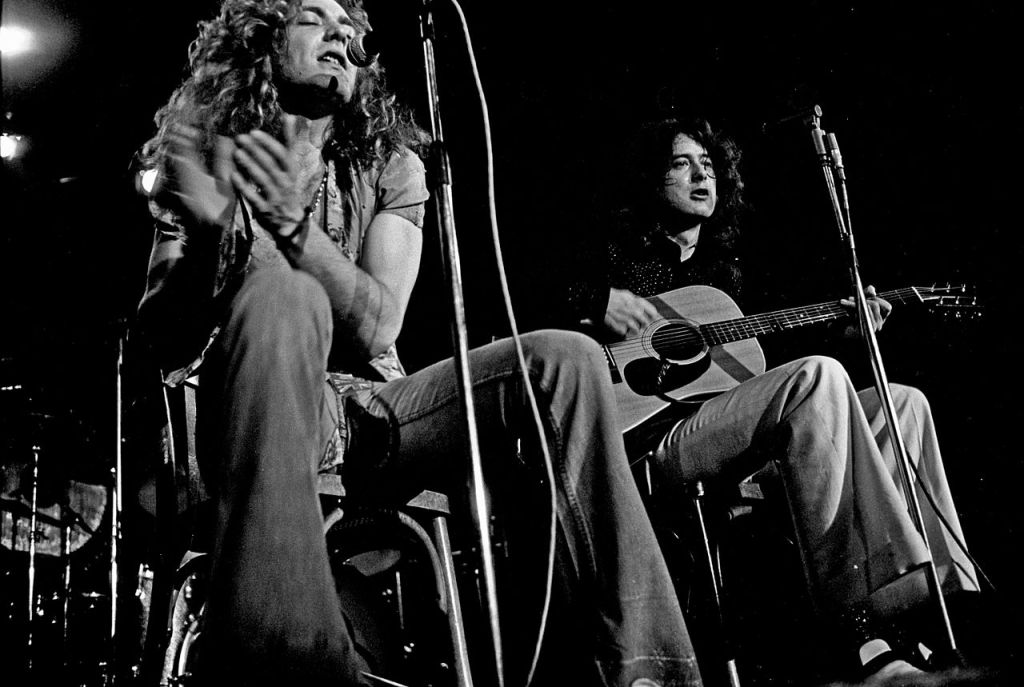 Black and white of Robert Plant and Jimmy Page of Led Zeppelin in 1979 sitting down singing and in concert.