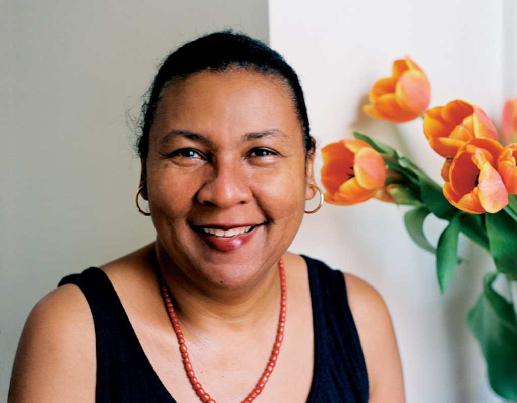 bell hooks head shot, smiling in a black tank top with orange beads and orange tulips toward the upper right, book review of The Will to Change