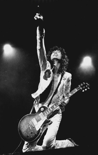 Jimmy Page of Led Zeppelin kneeling down pointing up with his guitar in concert.