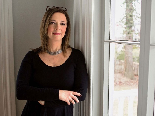 Susan Cain full portrait, dressed in all black leaning against a window pane, book review of Quiet, The Power of Introverts