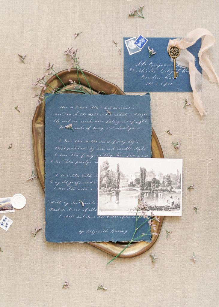 Items used for scrapbooking: an old, handwritten letter in blue paper over a gold photo frame and a black and white photograph over it used for scrapbooking.