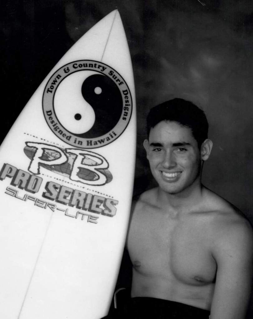 """Surfer """"Dito"""" posing shirtless with his Pro Series surfboard"""