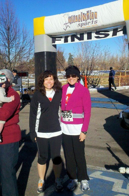 two women posing in front of a finish line sign after running a 5K
