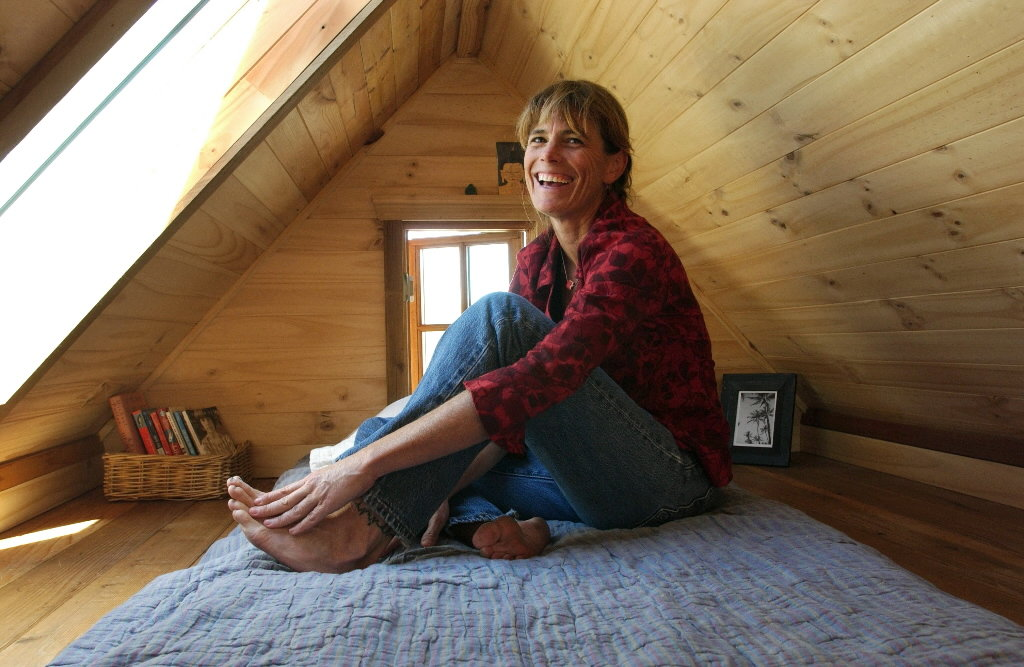 Dee Williams in her Tiny House sitting on her bed