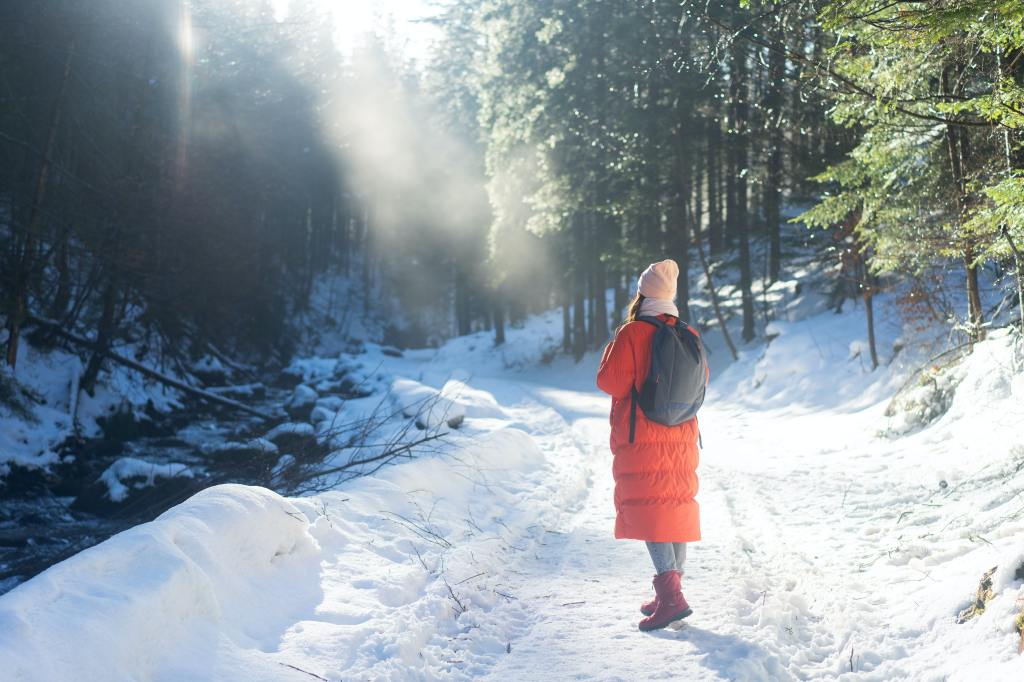 girl with think orange coat walking in winter, trees and snow on the ground