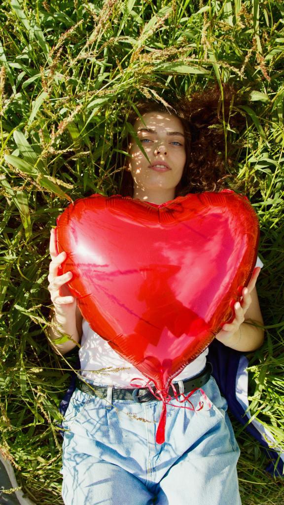 girl laying on grass holding a large balloon heart