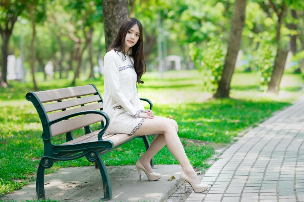 Asian girl sitting on a bench in the summer with trees in the background