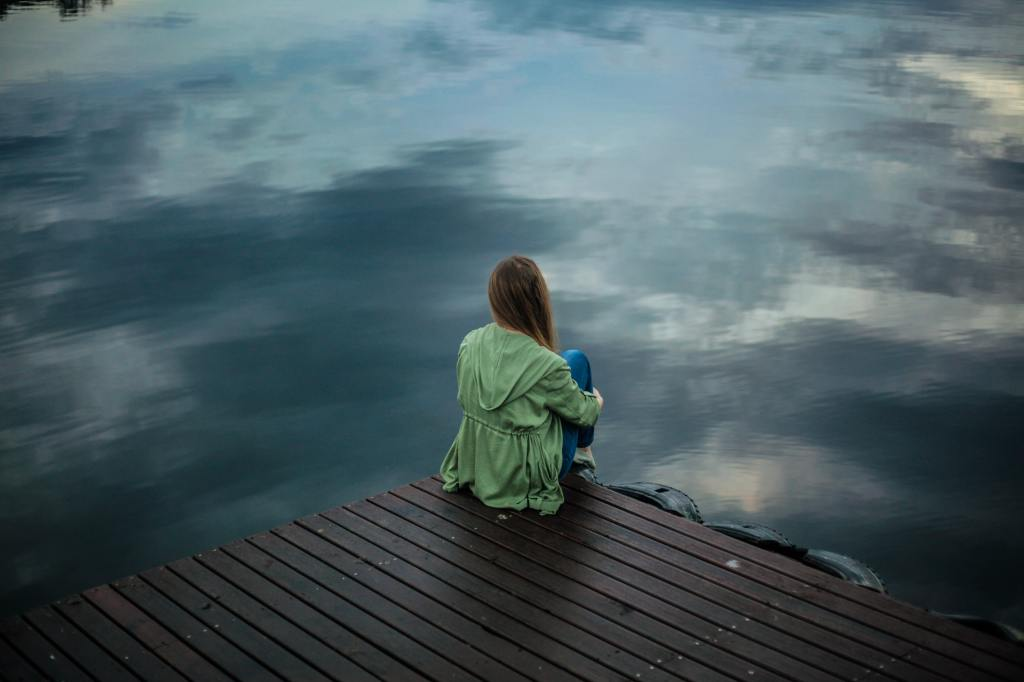 girl sitting on the edge of a roof with a troubled sky