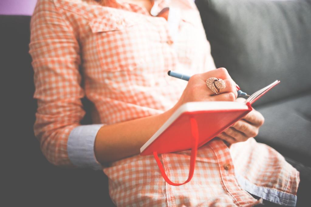lady sitting writing in an orange journal wearing an orange-checkered shirt.