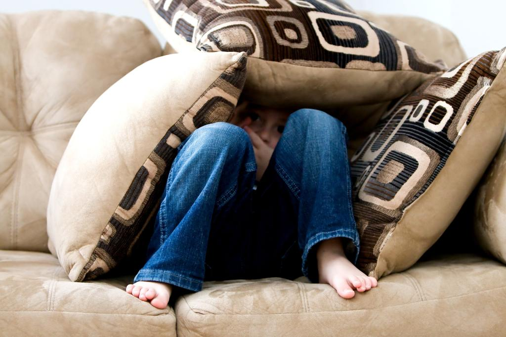 girl sitting on a light brown couch hiding her face in between pillows in fear