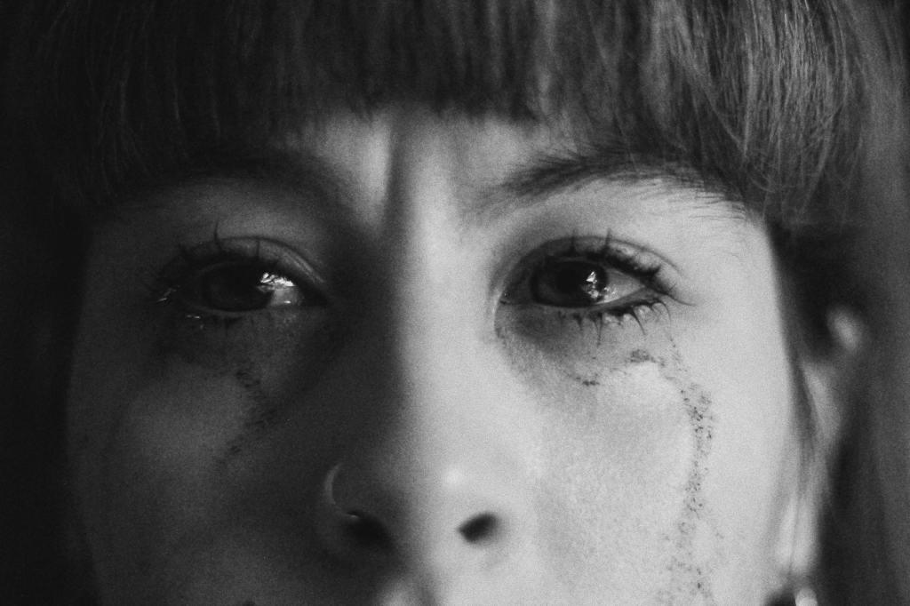woman's face. black short bangs crying and grieving