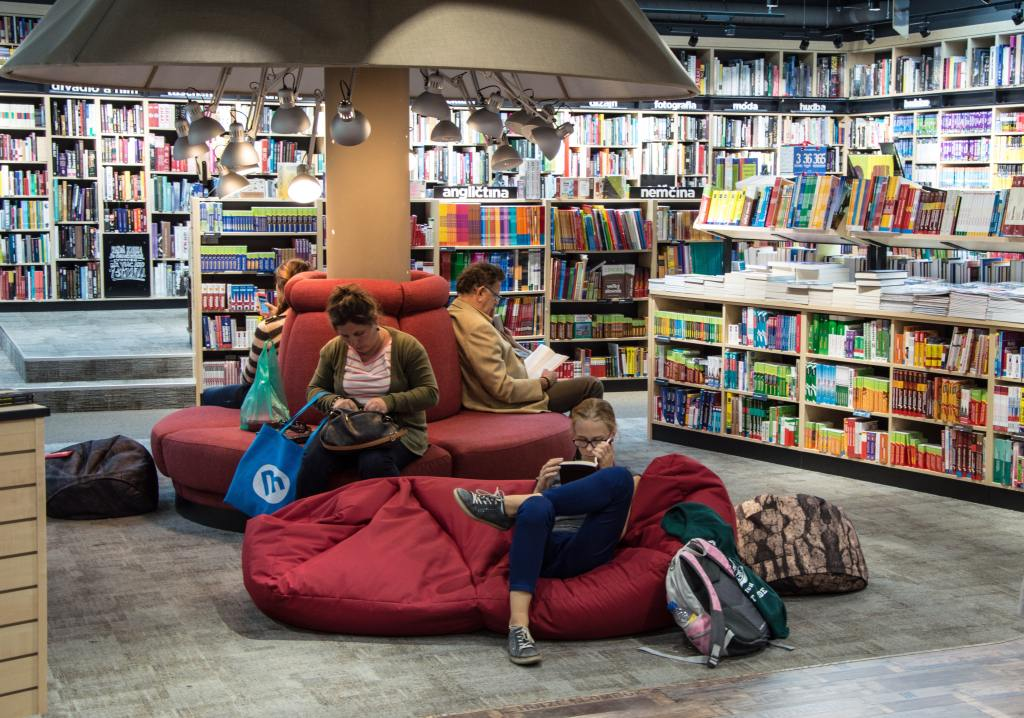 three people sitting reading in a book store
