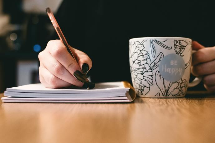 """woman journaling and having a cup of coffee with a mug saying """"be happy"""""""