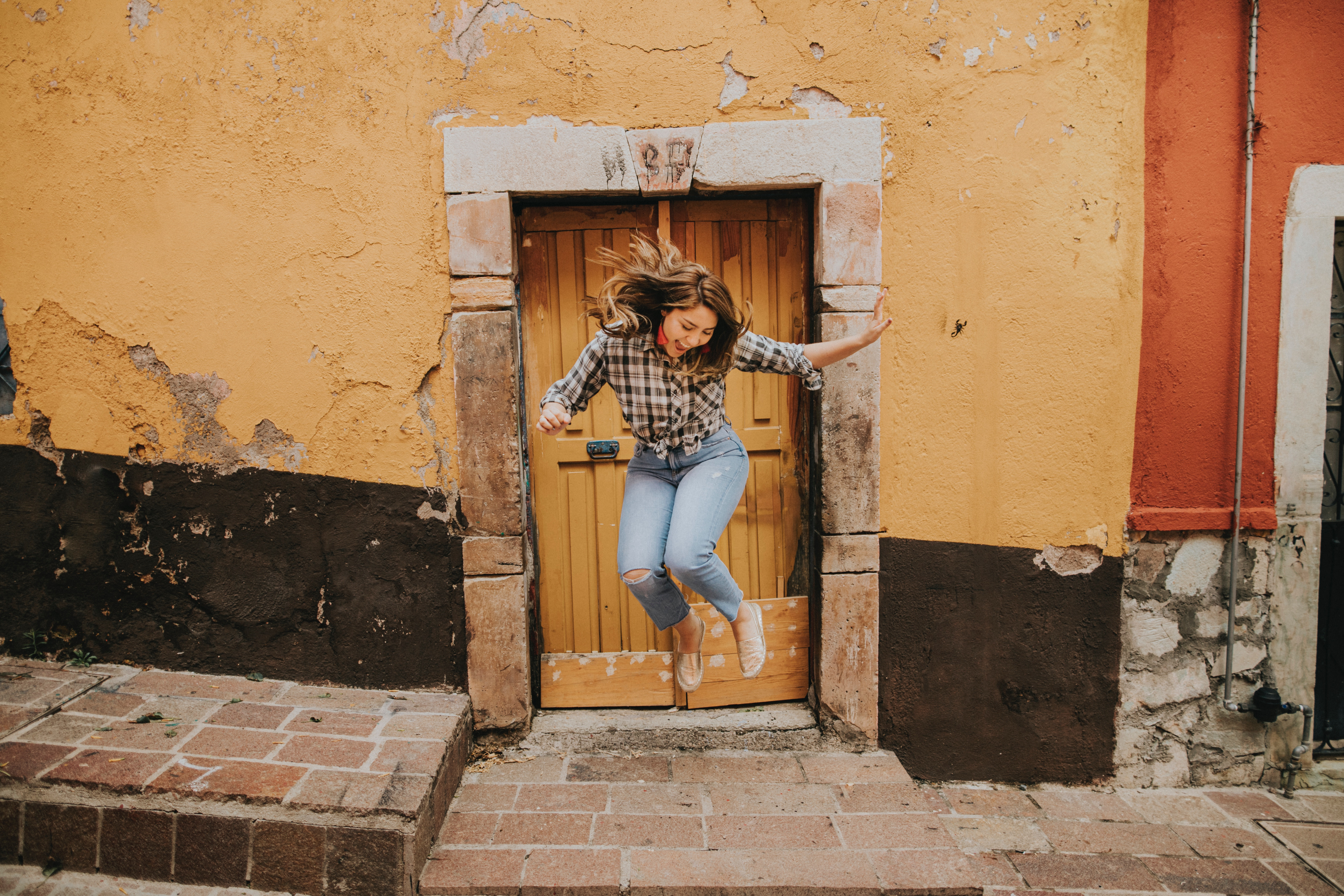 woman jumping in joy in front of the front door of a house