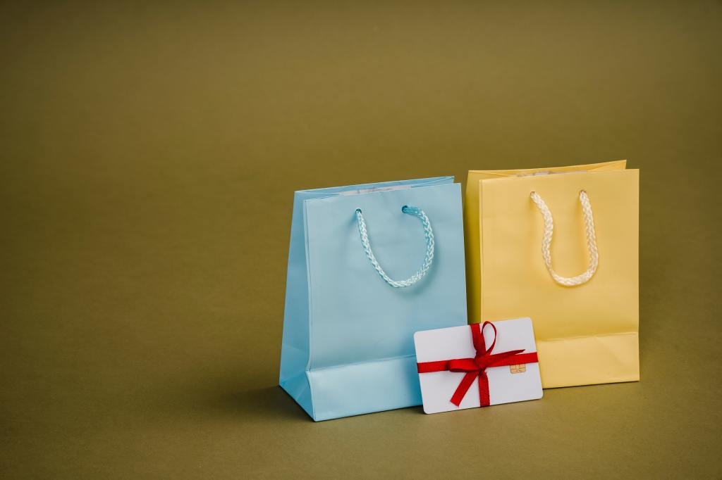 Two gift bags: one light blue and one yellow and a note in a red bow with them.
